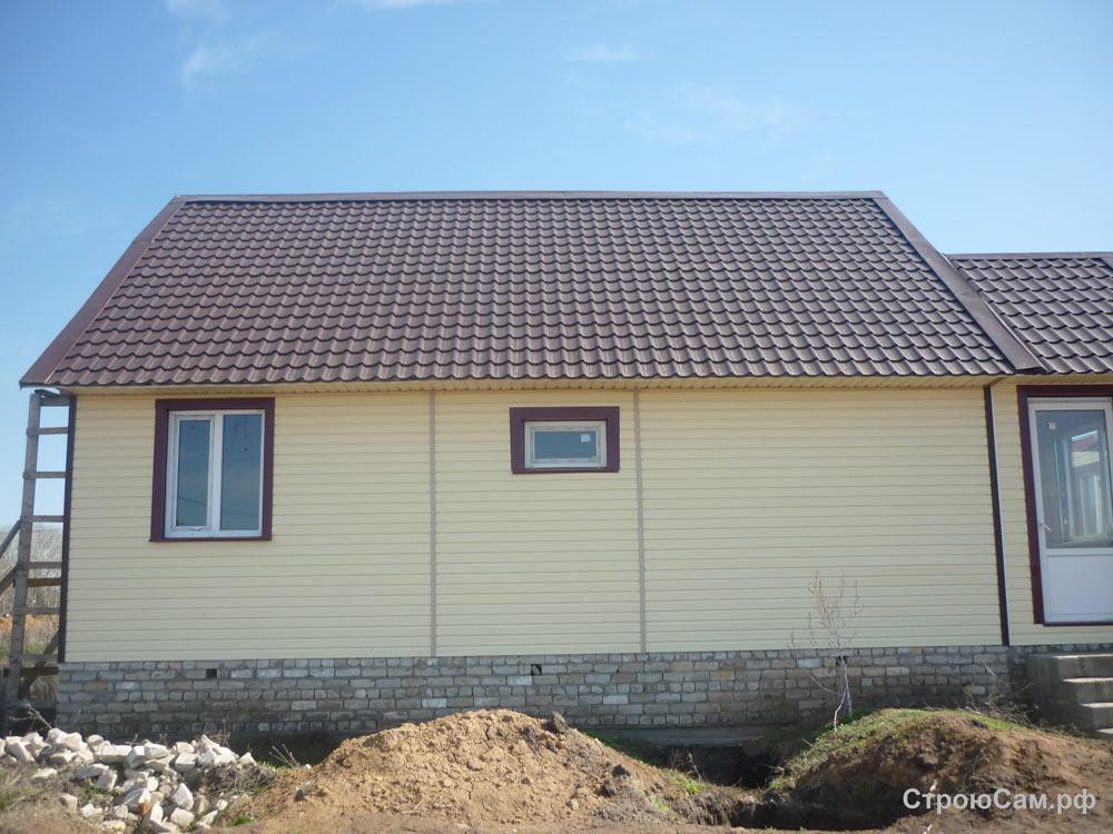 Стены покрыты виниловым сайдингом лимонного цвета, крыша - коричневой металлочерепицей