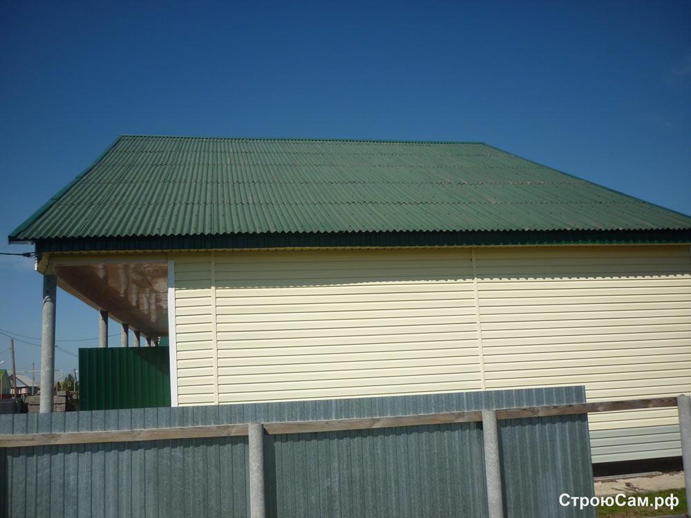 Стены облицованы виниловым сайдингом лимонного цвета, крыша покрыта темно-зеленым  ондулином.