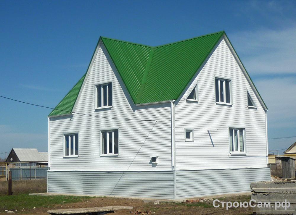 Стены облицованы виниловым сайдингом белого цвета, крыша покрыта светло-зеленым  металлопрофилем