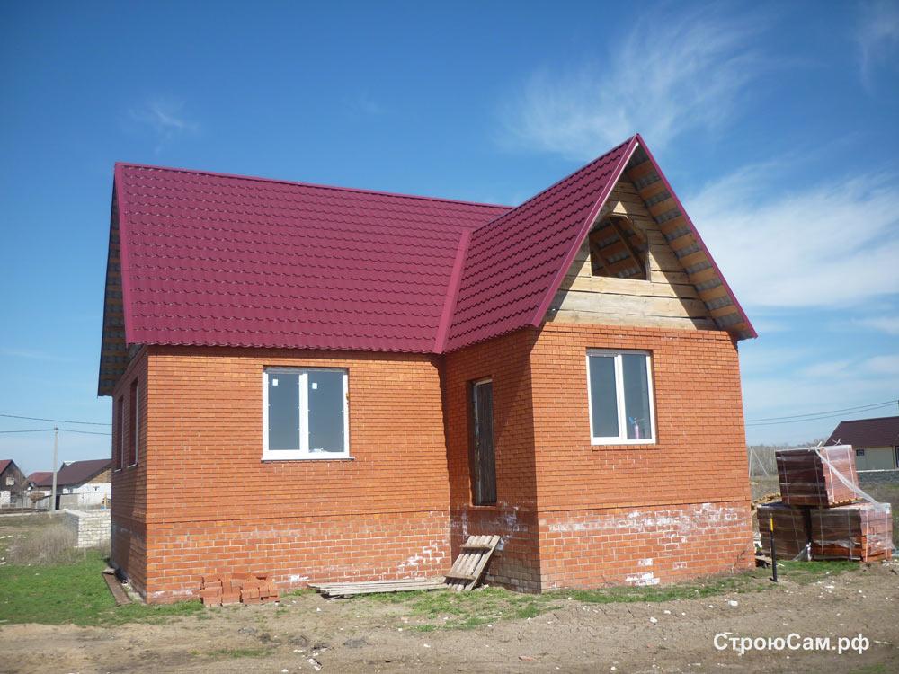 Стены из красного кирпича, крыша покрыта бардовой металлочерепицей