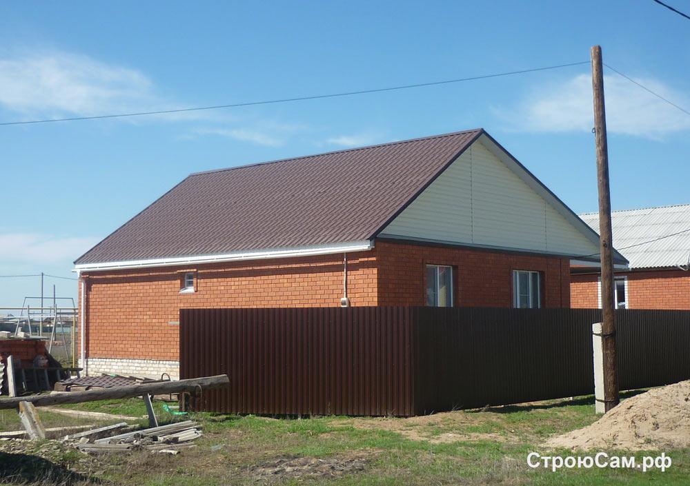 Стены из красного кирпича, крыша покрыта коричневой металлочерепицей